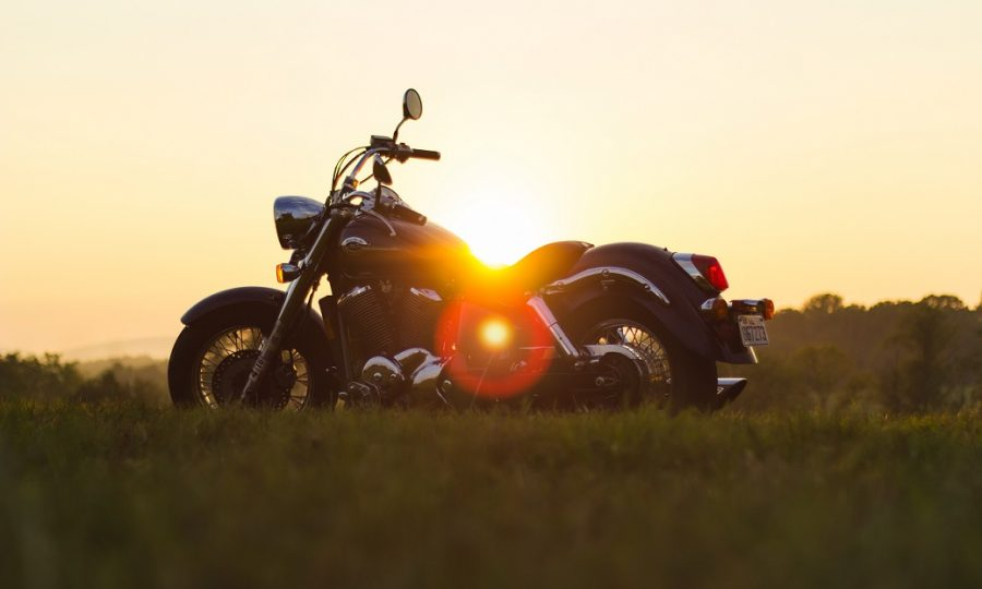 A motorcycle with the sun setting behind it.