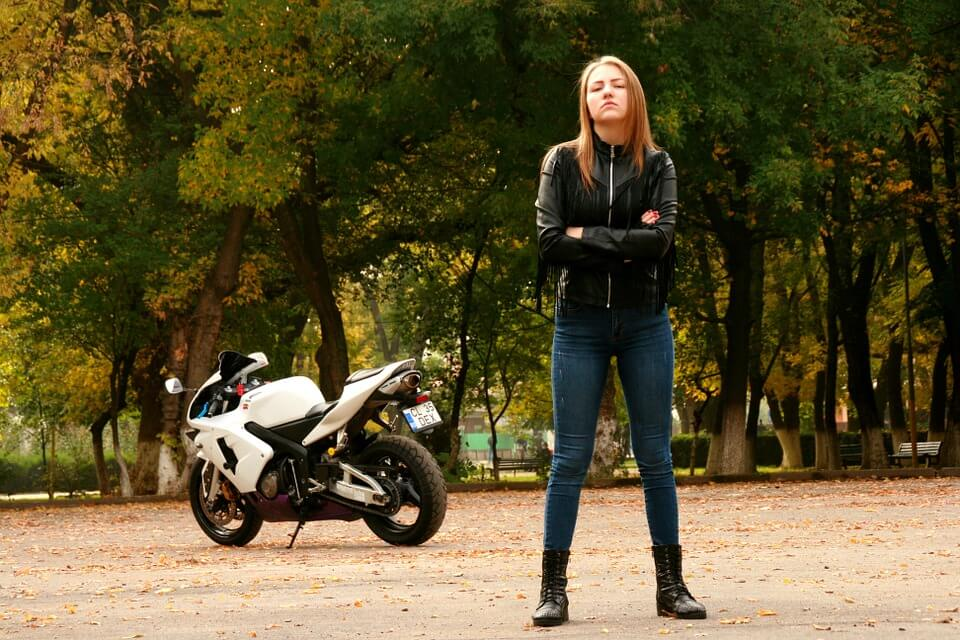 A young woman posing with her motorcycle in a leather jacket.